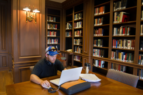 View of Safire room in Bird Library. A student seated at a large table with laptop. Behind him is a library.