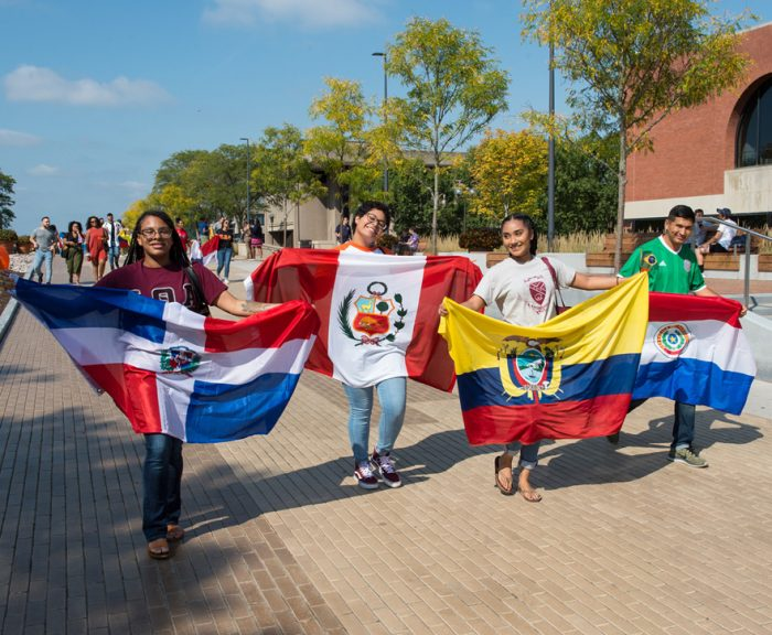Students holding flags walk down the Einhorn Family Walk for Latin x Hispanic Heritage Month opening parade.