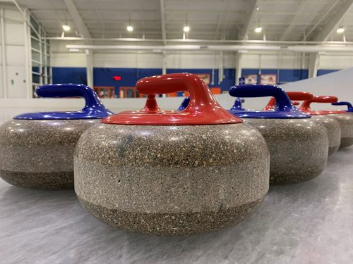 curling stones lined up on the ice at Tennity
