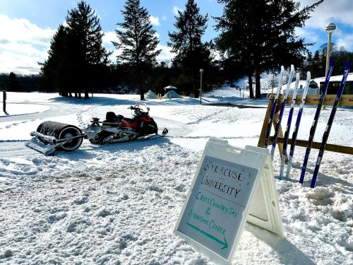 snow blankets drumlins country club and a display of skis at the cross country ski and snowshoe center