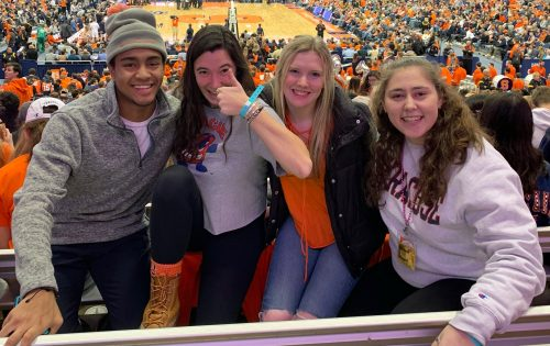Friends pose together at a men's basketball game