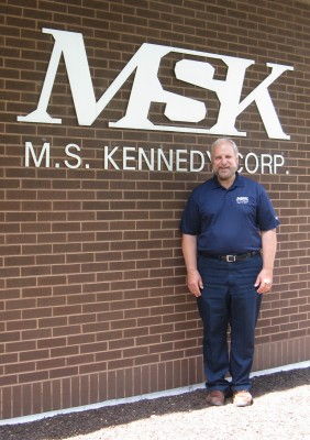 Michael Prockup stands in front of M.S. Kennedy.