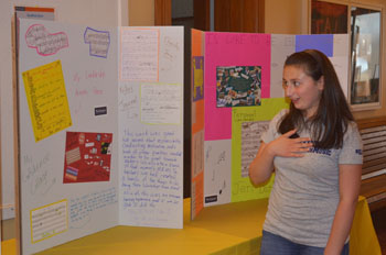 Liverpool High School student Julie Coggiola shares her projects and assignments on her presentation board during the last day of the Girls Leadership Academy for Music .