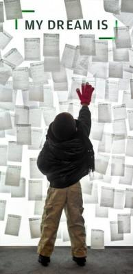 """A child posts his dream on a the illuminated Dream Wall of the King Imaging Project exhibition after writing it on a """"My Dream Is"""" card."""