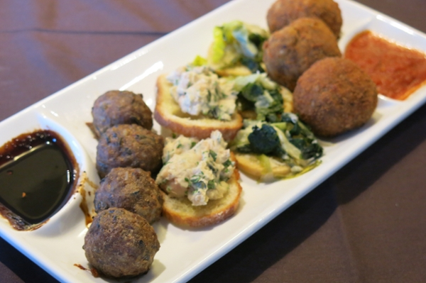 Turkey and wild rice meatballs, white bean dip and Utica greens on crustini and quinoa Arancini is served during a healthy cooking event in Boston for SU alumni and friends.