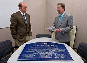 Joe Alfieri, left, and Eric Beattie look over the plaque honoring the airmen injured and lost during a catastrophic barracks fire more than 50 years ago on the University's South Campus. The plaque is part of a new memorial to be unveiled Friday, Oct. 4. Beattie is director of the Office of Campus Planning, Design, and Construction. Alfieri is a senior project manager in the office.
