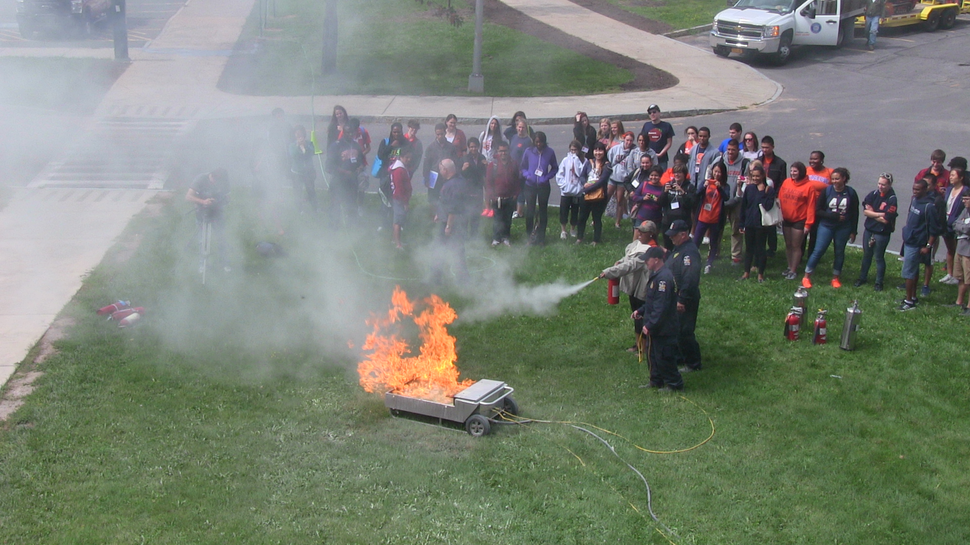 As part of fire safety training, residence hall staff learned how to use a fire extinguisher.  It's all done under the watchful eye of representatives from Syracuse University, the city of Syracuse, and New York State.