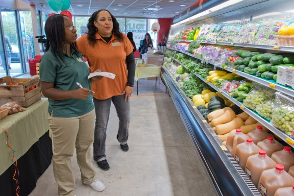 Eat to Live Food Cooperative employee Shannon Sescho, left, and Cathy Lobdell, assistant general manager, check inventory during the cooperative's grand opening on Oct. 15. Designed by architect Sekou Cooke, the 3,000 square-foot grocery store and café is located on South Salina Street and features healthy food and produce sourced from local farms and distributors.