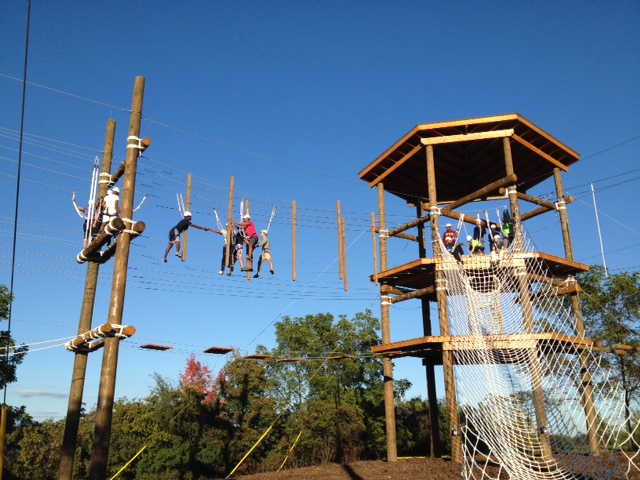 Part of the 'Cuse Challenge Course involves literally walking a tightrope.  If you look closely, you'll notice each participant is safely strapped in.