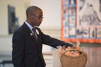 Remembrance Scholar Korey Tillman places tulip bulbs in a basket in Hendricks Chapel during the Convocation for Remembrance Scholars, honoring the 2013-14 cohort, on Oct. 11.