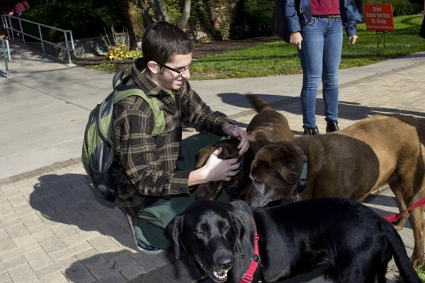 A perfect way to beat the stress of classwork, by taking a few moments for some canine companionship on the quad.
