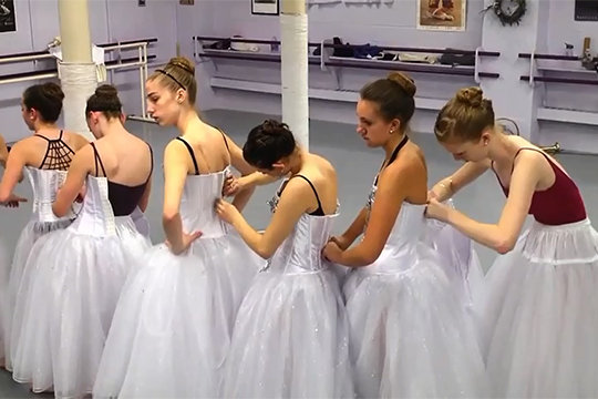 "Students from Syracuse City Ballet help each other into their costumes for a rehearsal of ""The Nutcracker."" Members of the SU community can get tickets for the production for a 10 percent discount."