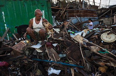 A man comforts his dog amidst the rubble of Typhoon Haiyan in his community, Tacloban city. More than two weeks have passed after Super Typhoon Haiyan caused widespread devastation across the region. Photo by Jacob Maentz for Corbis