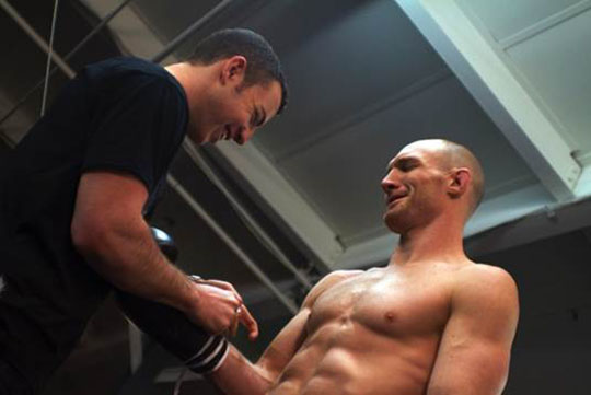 Daniel Goldberg helps UFC fighter Ryan Laflare lace up his Golden Gear gloves.
