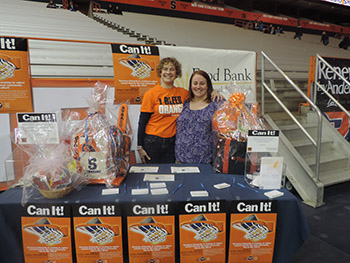 Bridget Yule, SU's director of student centers and programming services, and Lynn Hy, director of philanthropy at The Food Bank of Central New York, are pictured at the back court donation table during the Feb. 15 Can It! event.