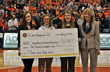 A check presentation took place during the SU men's basketball game on February 19 at the Carrier Dome. Picture L-R: Alyssa Wood, '13 auction co-chair; Kathleen Stress, Food Bank of Central New York, Executive Vice President; Carly Raimo, '13 auction co-chair; Kate Veley, SPM Club co-advisor.