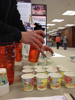 Sustainability Division intern Robbie Provenzano pours water into tasting cups. Without knowing which was which, most participants chose campus tap water as their favorite.