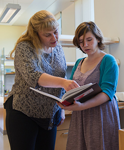 Katharine Lewis, left, works with a student.