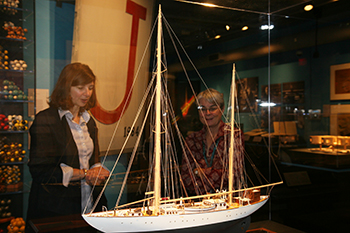 """Newton and Deborah Douglas, director of collections and curator of science and technology at The MIT Museum, study a model of the R/V """"Atlantis,"""" the first """"purpose-built"""" research vessel for oceanography. MIT is home to The Edgerton Center, named for one of Newton's mentors: Harold """"Doc"""" Edgerton."""