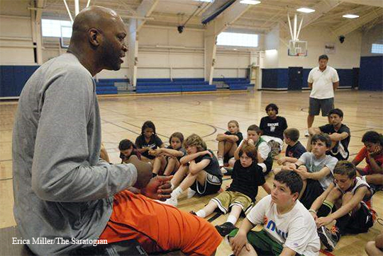 John Wallace speaks to youngsters at the Saratoga Rec Center during a basketball camp. He often reaches out to inspire young people.