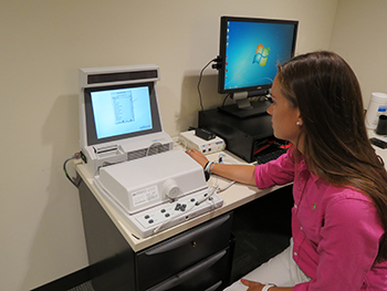 A graduate student operates the Audioscan Hearing Aid Analyzer, used to fit hearing aids at the Gebbie Clinic.