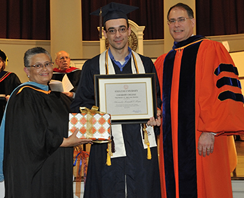 Alexander Kenneth O'Mara receives the Nancy Gelling Award, given to an Alumni Scholar with the Highest GPA. At left is University College Dean Bea Gonzalez, and at right is Syracuse University Provost Eric Spina.