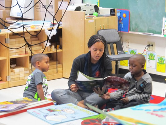 – Literacy Corps tutor Victoria Carpio '14, with the Falk College of Sport and Human Dynamics, shares a book with two students at Dr. King Elementary School.
