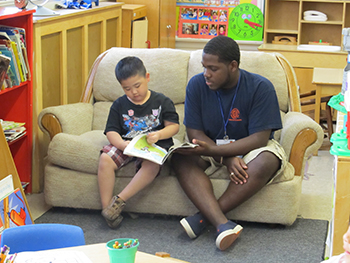 Sean Brown '15, who is with Falk College and the Whitman School of Management, tutors a youngster at Northside CYO's Pre-K program at Cathedral Academy at Pompeii. Brown is a member of the Literacy Corps.