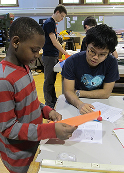 "Jiahao ""Jackie"" Lixue '14, with the College of Engineering and Computer Science, works on a project with a Danforth Middle School student as part of the engineering ambassadors program. In the background, Aaron Burlew '15 helps out another student."