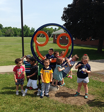 Children gather around the happy face sculpture created by Scott Gerber and installed recently near the Bernice M. Wright Lab School.