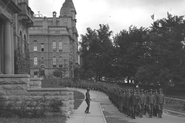 In this photo, circa 1918, the Students' Army Training Corps march in formation by the Hall of Languages. This is one in a collection of photos from Syracuse University Archives that show WWI activity on campus.