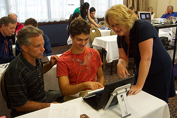 Darlene Hanson, right, a communication specialist from California, assists a non-verbal young man who communicates by typing on his iPad and his father in a Skill-Building workshop at the 2013 Institute on Communication and Inclusion Summer Institute.
