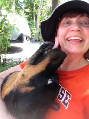 Barbara Jones, professor of practice at the Newhouse School, gets a kiss from her rottweiler.