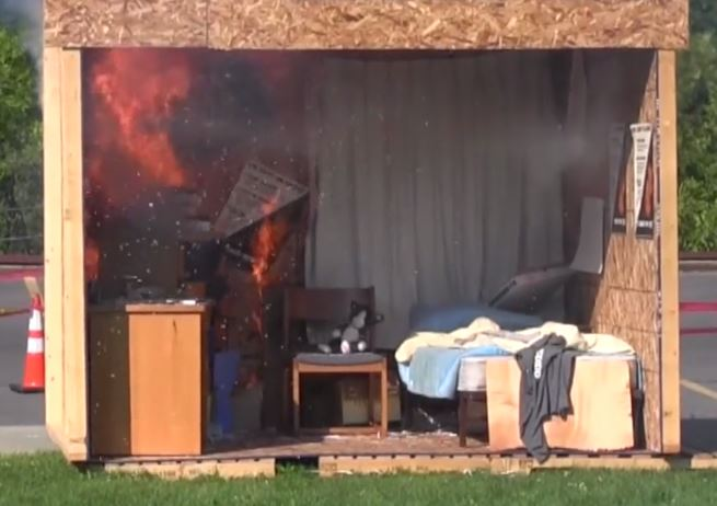 As part of the Residence Life Fire Safety Academy, a mock room is set ablaze.  Firefighters are standing nearby to extinguish the flames.