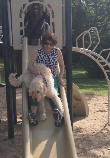 Kal Srinivas, director for retention, tries out the slide with Simba during a trip to Detroit. Her daughter, Nina Babu '03, claims the next slide.