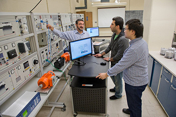 Prof. Tomislav Bujanovic confers in his lab with  students, Mohammad Mojdehi, center, and Liwen Sun.
