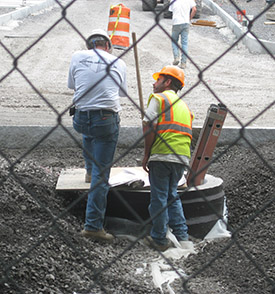 Workers confer on how to proceed on Sims Drive.