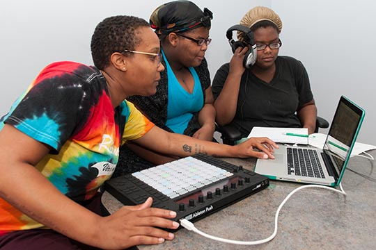 Sisters Na'eema and Jameira Harry work on rhythms under the direction of Syracuse University doctoral student Blair Smith, left, as part of the Writing Our Lives workshop held this summer at the Southside Communication Center.