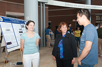 Le Moyne chemistry professor Anna O'Brien G'05, left, Syracuse interim dean of Arts and Sciences Karin Ruhlandt and Syracuse biology and chemistry professor Carlos Castañeda talk at the poster session.
