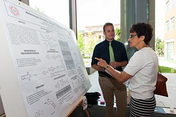 Le Moyne president Linda LeMura G'83, G'87 examines a science poster in Syracuse's Milton Atrium.