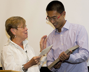 iSchool dean Elizabeth D. Liddy presents the Robert Benjamin Junior Faculty Achievement Award to Assistant Professor Yang Wang during the iSchool's opening convocation on Sept. 19.