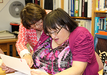 Mentee Angela Palimeri, right, participates in a hands-on clerical work experience in the FIXit office with mentor Linda Flynn at the Carriage House during Disability Mentoring Day.