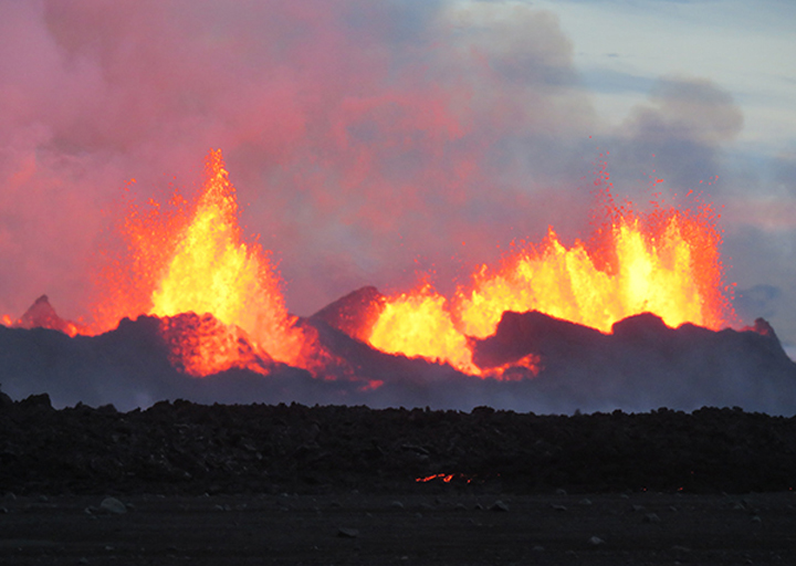 This evening view of a lava fountain at the volcano's central vent shows striking contrast between molten lava and surrounding rock and glacial ice. Erupting lava is thrown 50-100 meters into the air above the vents.