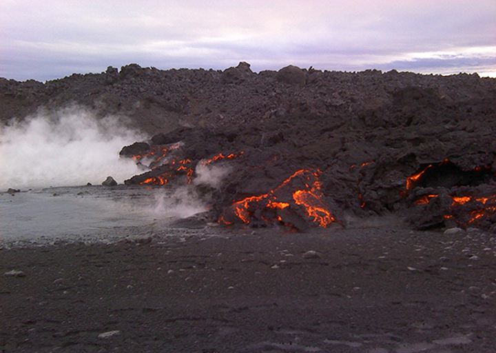 Fire meets water. Incandescent orange lava magnifies the cracks in the black outer crust of solidified lava. Steam forms when the lava flows into a nearby river.