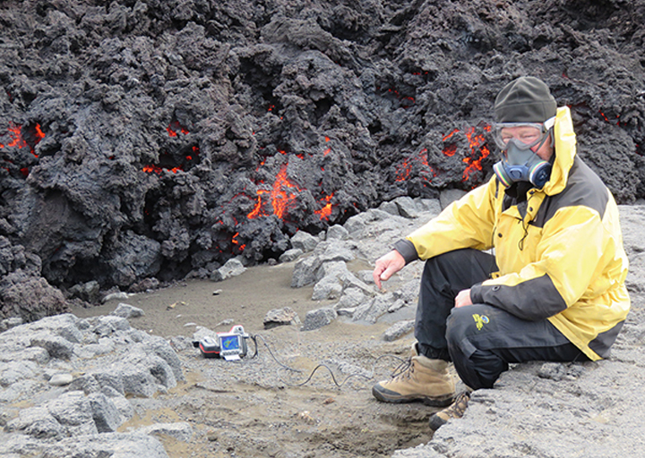 Jeffrey Karson on the ground at an active lava flow lobe, works with instruments for making infrared camera measurements. Gas masks and eye protection are required because of hot, poisonous volcanic gases and wind at the eruption site.