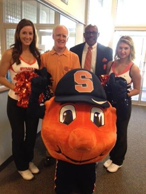 Syracuse Common Councilor Bob Dougherty, second from left, and Floyd Little pose with a couple of SU cheerleaders and Otto after Sept. 29-Oct. 3 was proclaimed Orange Out Week.