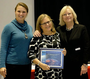 College of Law Professor Arlene S. Kanter, center, who received the International Educator of the Year Award by the International Center of Syracuse, is joined by Amy McHugh, ICS Board of Directors vice president, left, and Elane Granger Carrasco, ICS Board of Directors president.
