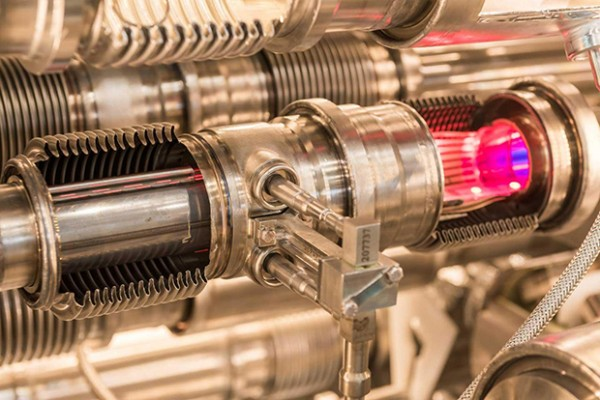 A pink glow illuminates the inside of this model of the LHC beam pipe, which is used to train engineers and technicians. ( Photo by Guillaume Jeanneret/CERN)