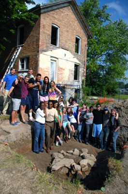 Members of the 2012 Syracuse University Field School gather at the excavation site of Tubman's well, with her brick house in the background. The photo includes University students along with the Reverend Paul Carter and Christine Carter of the Harriet Tubman Home. Syracuse University Field School is directed by Douglas Armstrong.