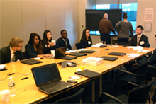 Student team members prepare to make formal presentations about their classwork, a policy risk assessment, to top EY executives.